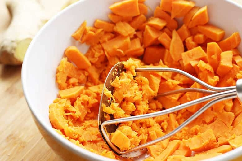 Cooked sweet potatoes being mashed in a bowl.