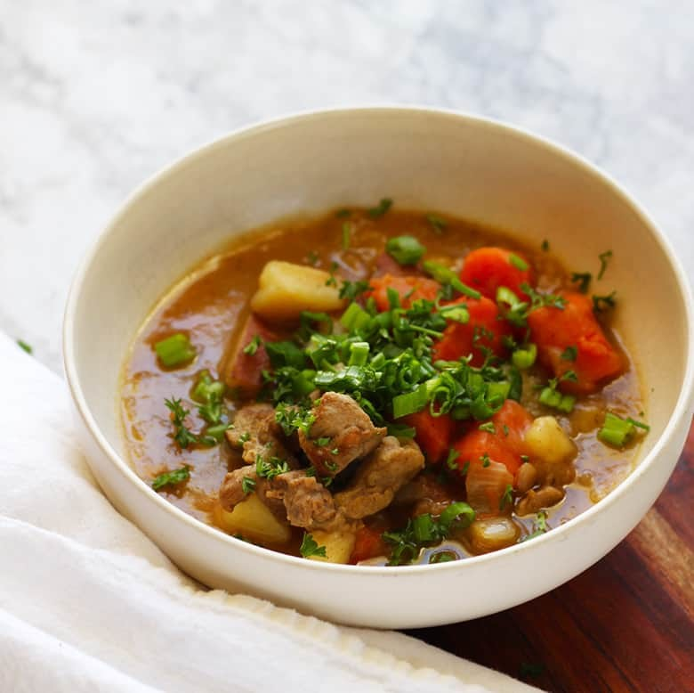 A bowl of Lamb Irish Stew garnished with fresh herbs.