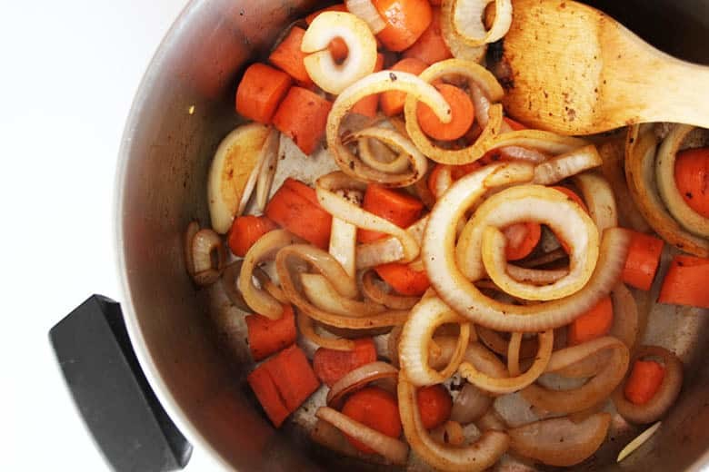 A pan of carrots and onions with the brown bits from the fond.