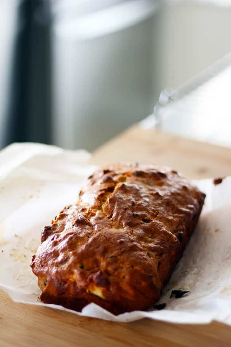 Golden brown apple and mince bread loaf on a cutting board.