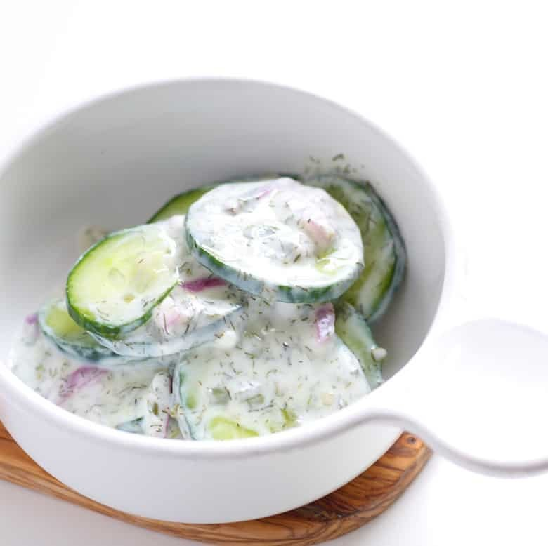 A bowl of cucumber salad in a white bowl.