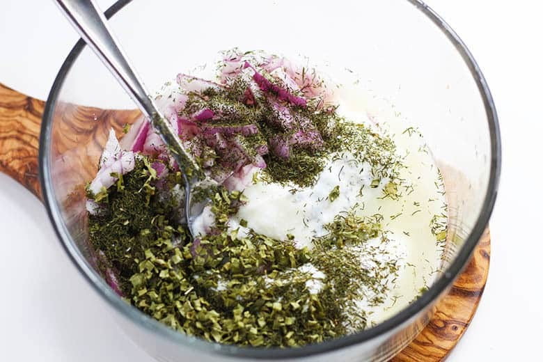 Yogurt, dill, onions and lemon juice in a mixing bowl.