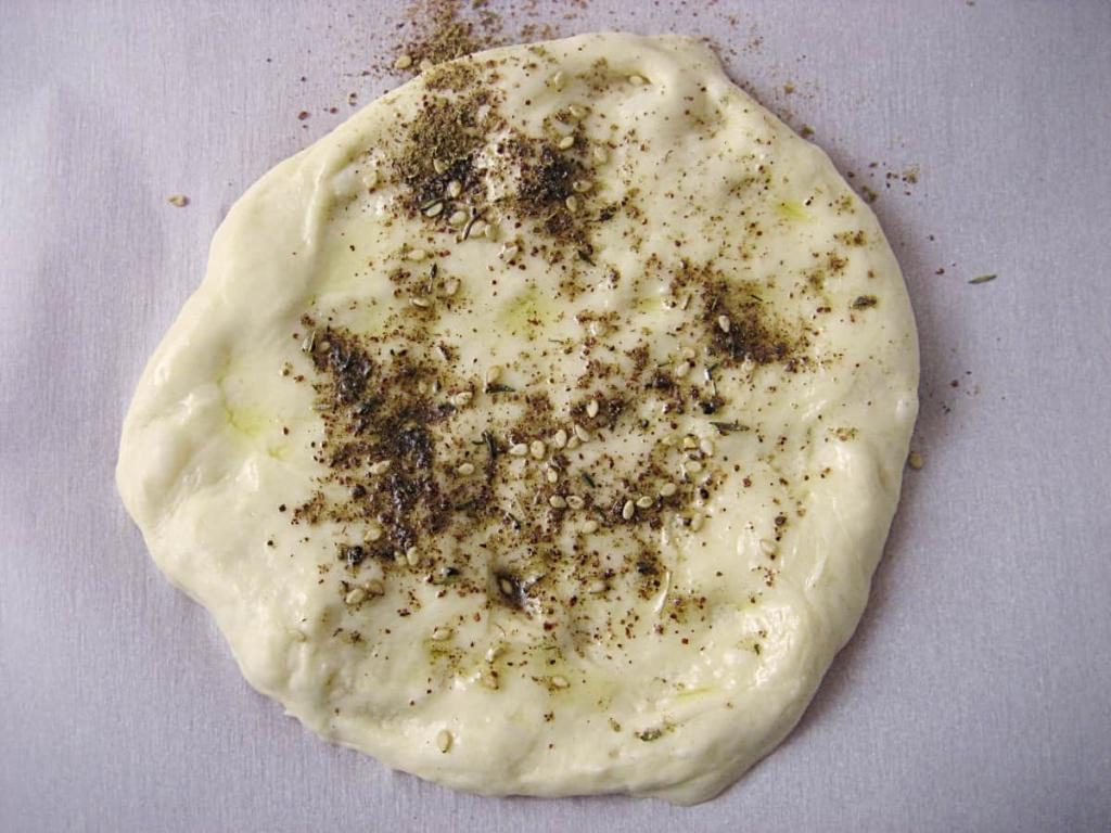 Spread dough with fingers and season with olive oil and Za'atar.