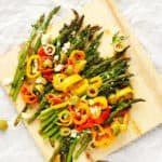 Roasted Spring Asparagus | with sweet peppers and feta. A Mediterranean inspired dish to welcome in Spring and Easter Sunday. Drizzled with olive oil, tossed with fresh herbs and garlic and garnished with sweet peppers and olives. Oh my YUM!!! | FusionCraftiness.com
