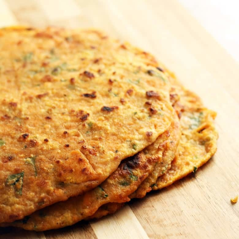 A pile of cooked parathas on a cutting board.