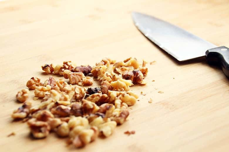 Chopped walnuts on a cutting board.