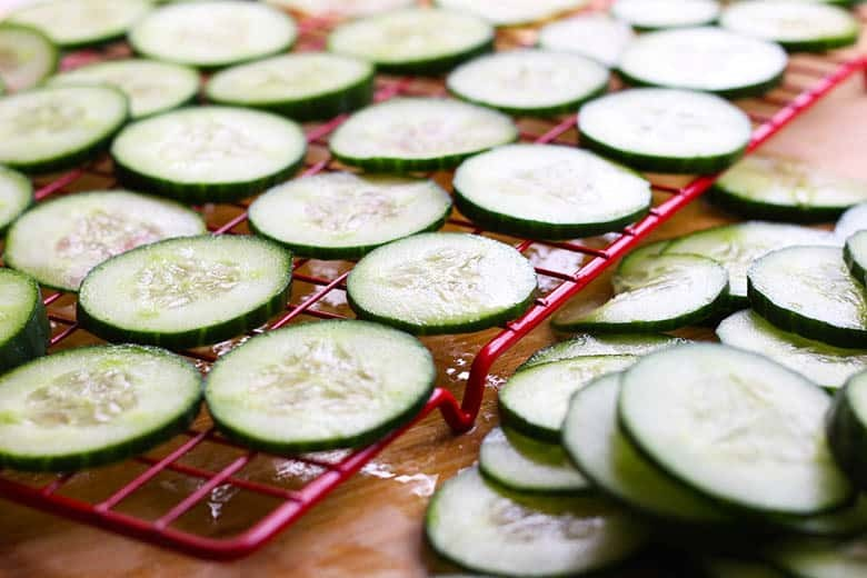 Sliced cucumber on a red cooling rack.