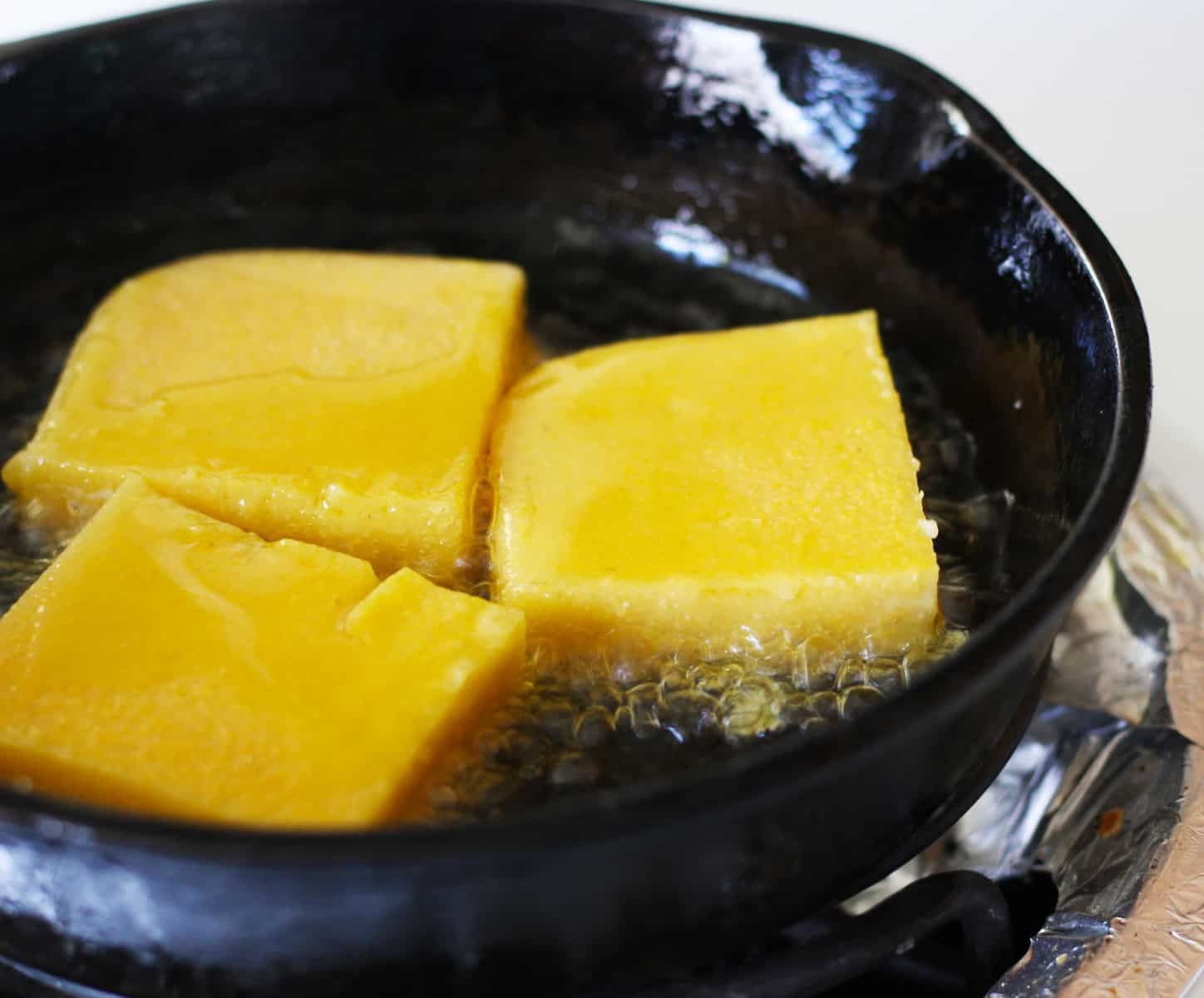 Polenta frying in a pan.