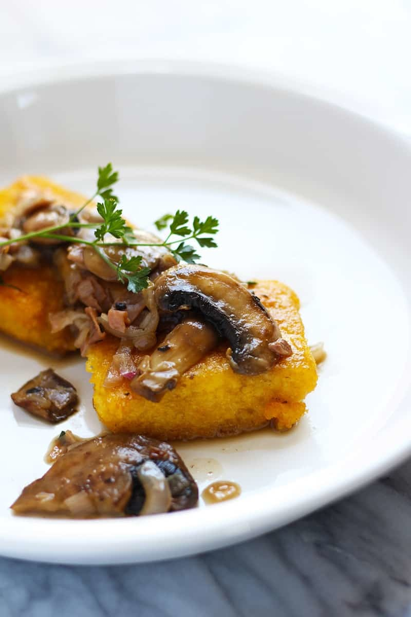 Fried polenta cake on a plate with mushrooms.