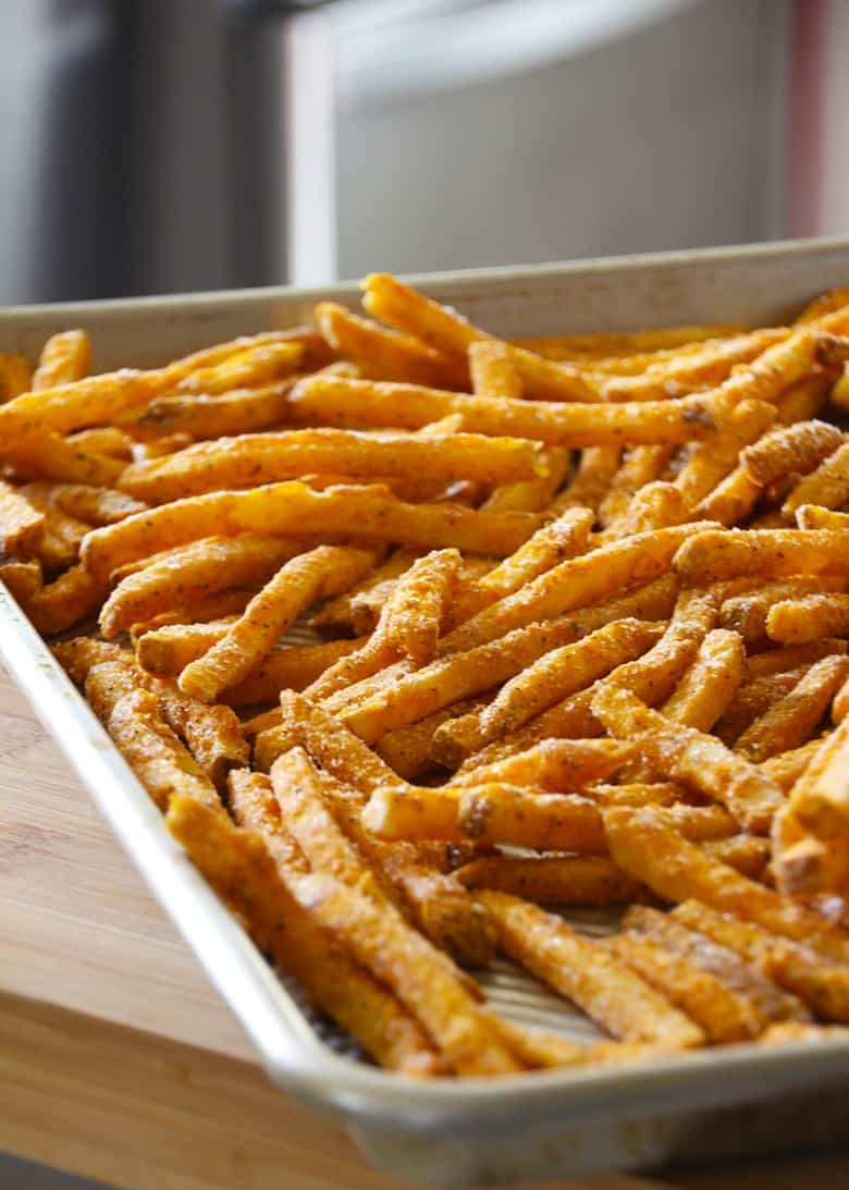 Frozen fries on a baking sheet.