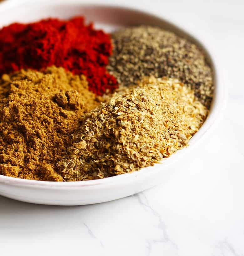 A plate of cumin, coriander, paprika and black pepper.