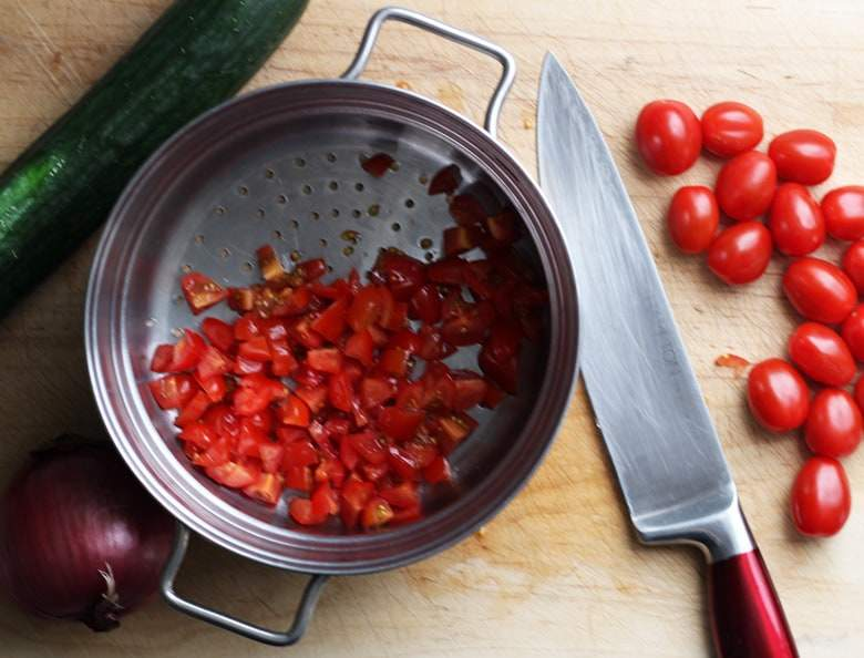 Chopped tomatoes in a sieve.