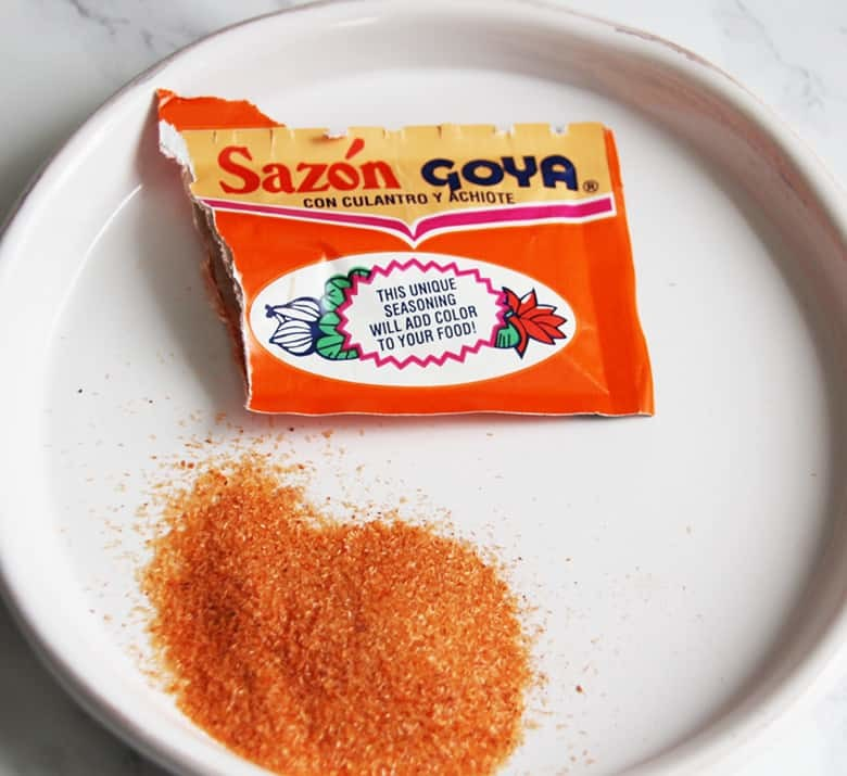 A packet of Sazon Goya con cilantro Y achiote on a white plate.