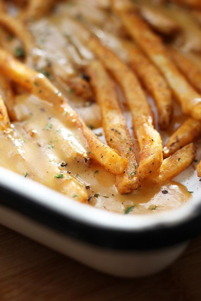 A white pan of fries with rarebit sauce.