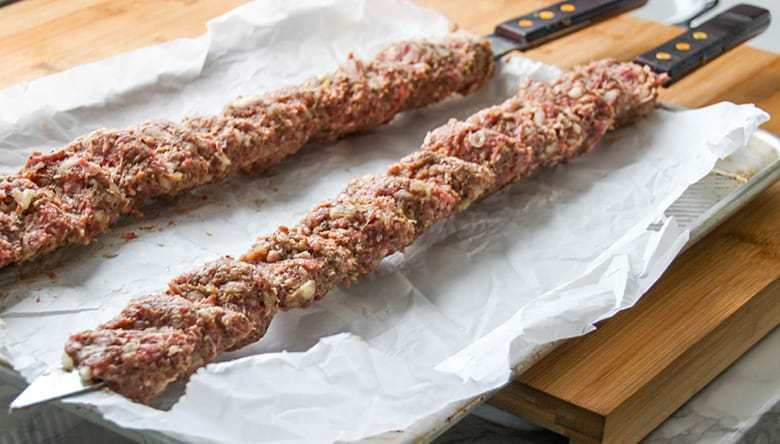 Raw ground meat on a skewer.