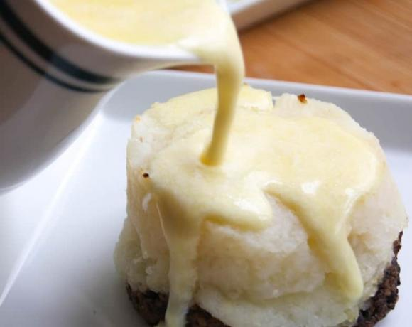 Whiskey butter sauce pouring over a haggis stack.