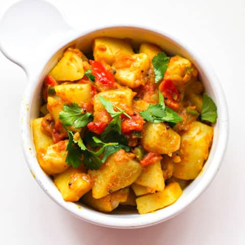 Yellow Bombay Potatoes in a white bowl.