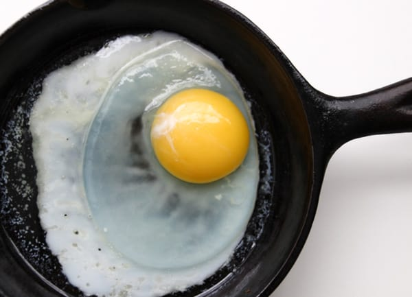 Single egg cooking in a black skillet.