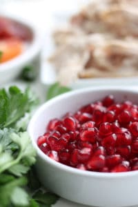 Pomegranate seeds in a white bowl.