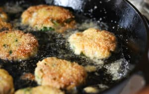 Salmon Croquettes frying in a cast iron skillet.