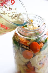 Pouring water into mason jar full of vegetables.