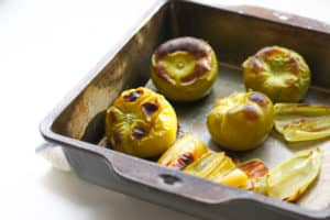 Roasted tomatillos in a baking pan.