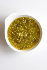 A bowl of green salsa.