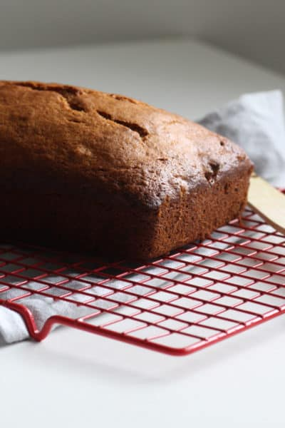 A golden loaf of banana bread on a cooling rack.