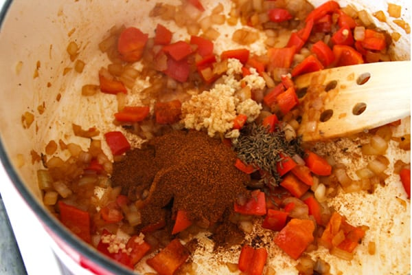 Adding spices and garlic to pot.