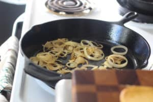 Thinly sliced onions frying in a pan.