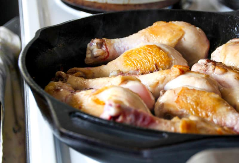 Chicken drumsticks browning in a skillet.